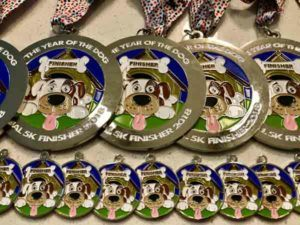 Year of the Dog Virtual 5k Race Finisher medals stacked on top of each other with matching medal for your dog